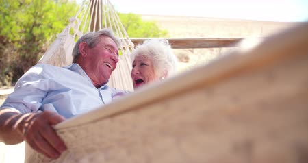 смеющийся : Slow motion video of a loving retired senior couple swinging in hammock and laughing together Стоковые видеозаписи