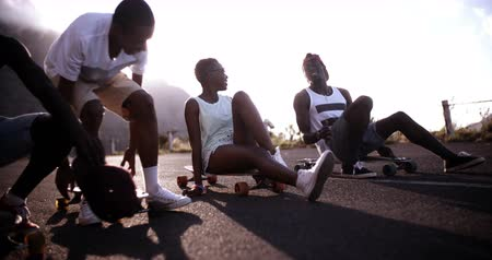 longboarder : African American girl with friends sitting on their longboards laughing in Slow Motion Stock Footage