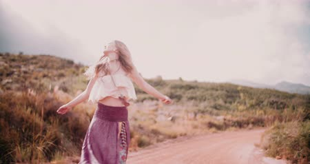 hippi : Boho girl dancing joyfully on a country dirt road in a summer landscape Slow Motion