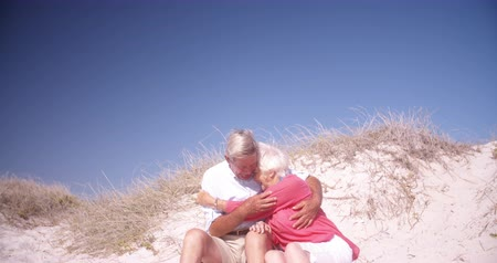 életerő : Hugging senior couple sitting happily on a sand dune at the beach together