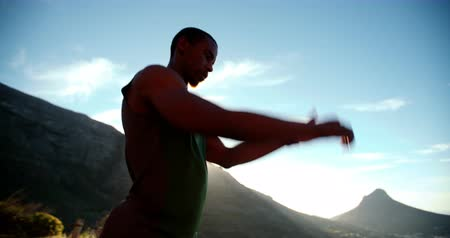 male : Focused runner stretching his arms and jumps in slow motion with sun flare over mountain