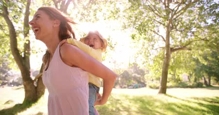 outdoor : Happy mom laughing while piggybacking her little toddler girl through a sunny park in slow motion