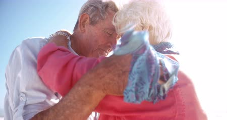 emekli : Affectionate elderly active seniors hugging lovingly on the beach in Slow Motion