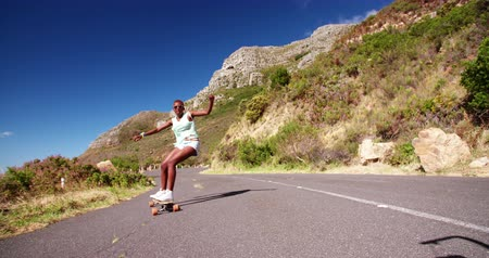 longboarder : Teen African American girl doing some downhill racing on her longboard in Slow Motion Stock Footage