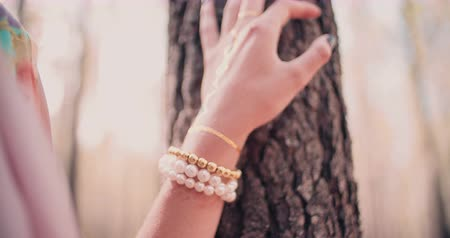 biżuteria : Cropped image of a womans hand with gold jewelry and a gold foil temporary tattoo resting on a tree trunk in a forest in Slow Motion