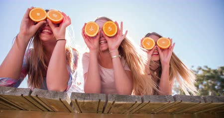 друг : Laughing teen girl friends lying on a wooden jetty holding up oranges over their faces for eyes Panning in Slow Motion