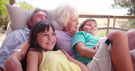 emekli : Loving grandparents spending time sitting with their grandchildren on their porch on  a summer holiday in Slow Motion Stok Video