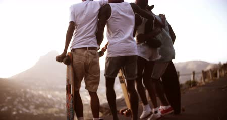 longboarder : Rear view shot of a group of american teen friends dancing happily together with their longboards in Slow Motion Stock Footage