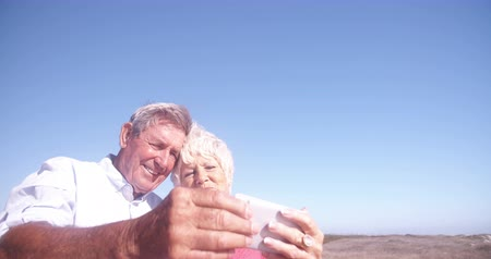életerő : Candid shot of a laughing elderly retired couple both holding their phone and taking a selfie Stock mozgókép