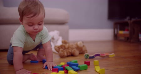 blokkok : Innocent looking baby boy chewing on a colorful building block in the middle of the living room Slow Motion