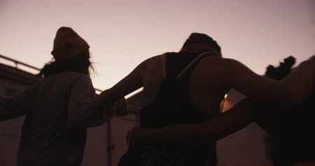 rebelião : Rearview shot of teen girl friends with grunge style running at twilight together in an urban setting in Slow Motion