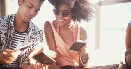paylaşımı : African american couple sitting with friends at the beach sharing instant photographs of fun memories of the summer in slow motion