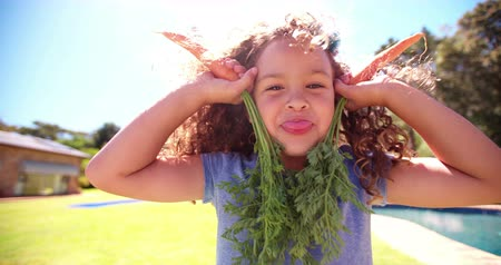 Cute little curly girl laughing and posing playfully holding up carrots as ears