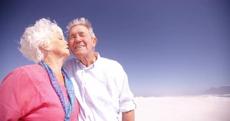 életerő : Affectionate elderly active seniors kissing lovingly on the beach Panning in Slow Motion