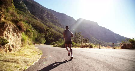 exercícios : Slow motion video of an athlete running outdoors for exercise and fitness on a road in the early morning sun
