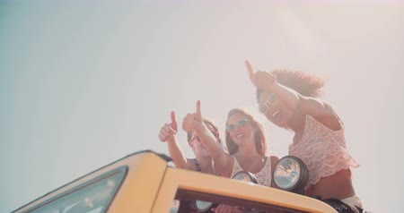 viagem por estrada : Afro girl and friends standing in their vacation vehicle posing happily a thumbs up while on a summer road trip Stock Footage