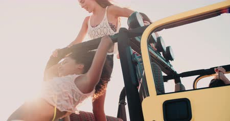 運輸 : Happy Afro girl and friend getting out of car at the beach on a road trip  in Slow Motion