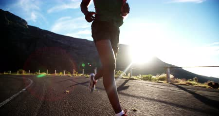 egészség : Running feet of african american male runner on mountain road on sunny day in slow motion