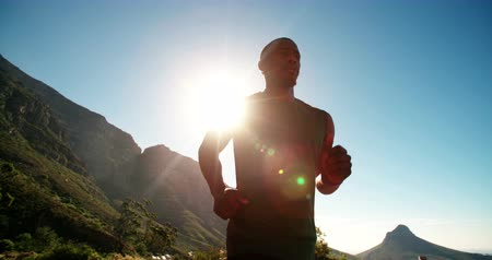 африканского происхождения : Wide angle slow motion video of an athlete running along a road with a bright sun and intense sky behind