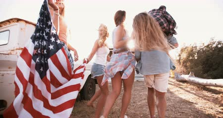 vlastenectví : Full length shot of a group of American teens walking together with a flag over their shoulders into sun flare Panning in Slow Motion