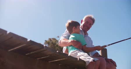 Retired grandfather sitting on a jetty teaching his grandson to fish Panning in Slow Motion
