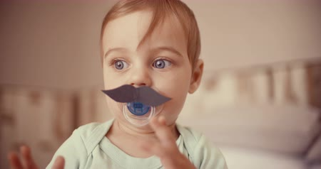 mustache : Sweet baby boy touching a paper mustache thats been stuck onto his pacifier Stock Footage