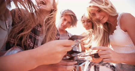 paylaşımı : Group of teenagers sharing instant photographs amongst themselves outdoors Panning in Slow Motion
