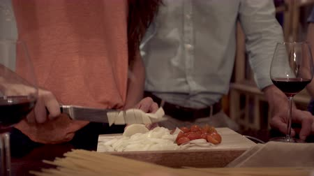 aşçılık : Closeup of woman cutting tomatoes and onions for italian pasta recipe husband standing next to her Stok Video