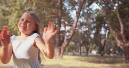 bolha : Happy little girl smiling and running with bubbles in a park in slow motion
