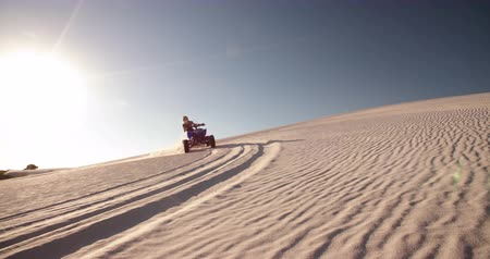 extremo : Competitive quad bike racer kicking up sand while driving up a sand dune on a summer evening with sun flare Slow Motion Panning Vídeos