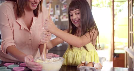 juventude : Little girl helping her mom in the kitchen by stirring the ingredients for their cake with a wooden spoon