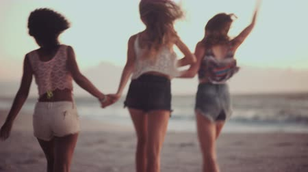 despreocupado : Three girls running happily while holding hands on a beach after sunset