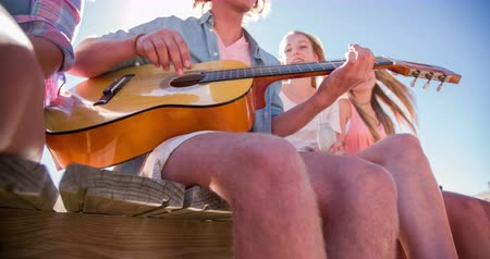 друзья : Teen guy playing guitar for his friends while sitting outdoors on a jetty on summer vacation Стоковые видеозаписи