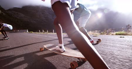 longboarder : Mixed group of teenaged longboarders racing each other downhill on a mountain road in Slow Motion