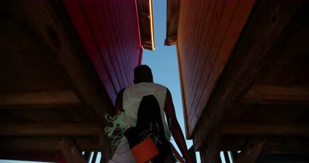 longboarder : Cool African American girl longboarder walking through colorful beachhouse at the beach in Slow Motion