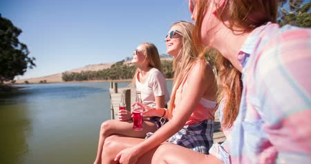 дружба : Group of teen girl friends sitting on a jetty laughing together while enjoying a summer break Panning in Slow Motion