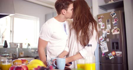 mutfak : Couple kissing romantically in the morning in their kitchen in Slow Motion Stok Video