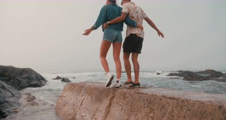 candid laughter : Rear view of a hipster couple walking together on a sea wall and helping each other balance slow motion Stock Footage