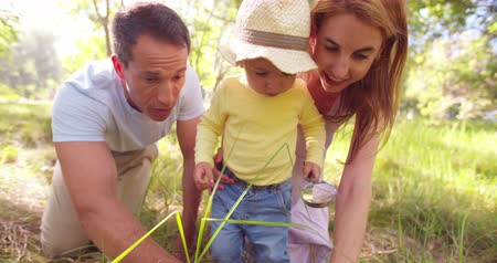 ajoelhado : Loving parents kneeling on the ground teaching their toddler all about nature