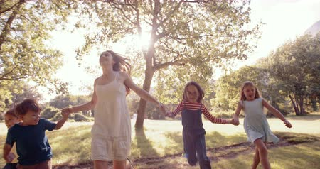 parque : Young mother running with kids  holding hands through a sunlit park in slow motion