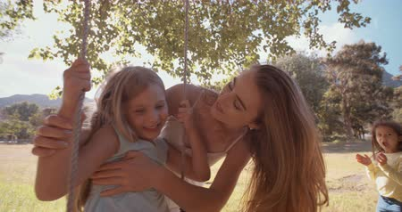 beijos : Mother hugging her daughter tightly on a swing and smiling in a sunlit park slow motion