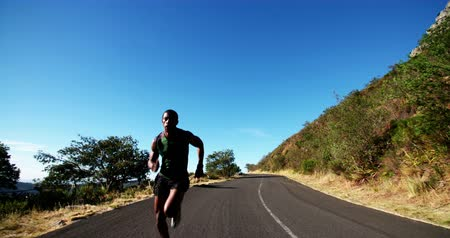 подготовке : Slow motion shot of athlete sprinting along road outdoors on a bright morning in his fitness training