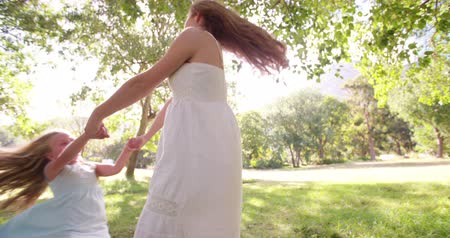 matka dziecko : Happy mom and daughter having fun spinning slow motion together in a natural park Wideo