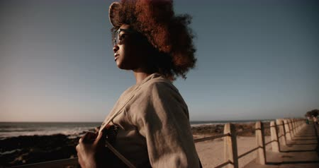 fiatal felnőttek : Fashionable Afro hipster teenager looking at the beach while standing on a walkway in Slow Motion