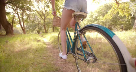 bisiklete binme : Girl cycling through a field in summer in Slow Motion