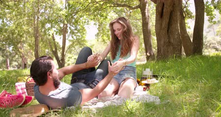 łaskotanie : Playful young couple laughing and tickling each other while having a picnic in the park Wideo