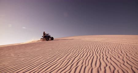 atv : Competitive quad bike racer kicking up sand and dust while traveling up a sand dune Panning in Slow Motion