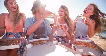 elvihető : Teen friends sitting outside enjoying pizza and laughing together on a bright summer day Stock mozgókép