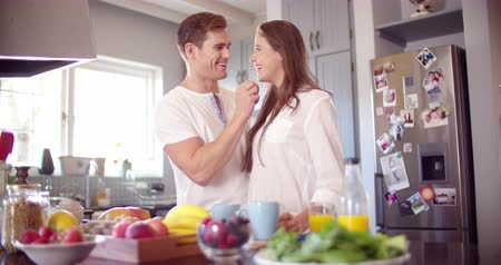 feed on : Loving boyfriend feeding his smiling girlfriend a fresh berry in their kitchen while making breakfast in Slow Motion