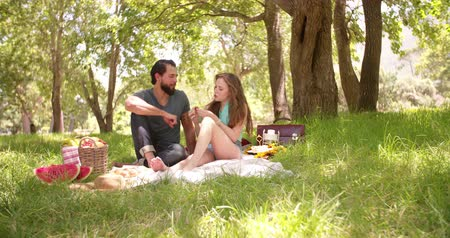 feed on : Smiling couple happily having a picnic in the park and playfully feeding each other fruit